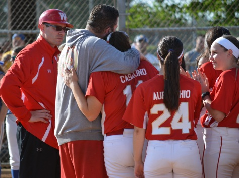 Head coach Bill Mitaritonna, left-center, consoles his senior pitcher, Francesca Casalino, and the rest of his team after the Colts fell to East Meadow on Friday in the Class AA Long Island championship.